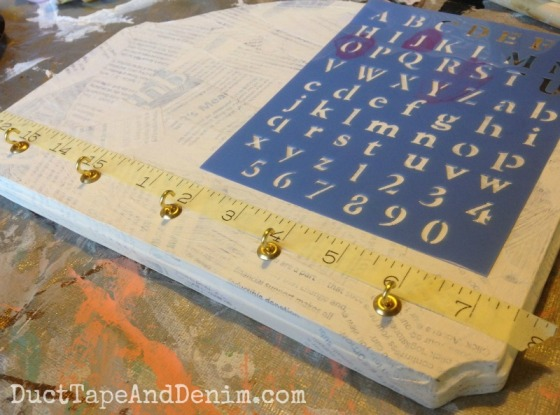 Adding cup hooks and stenciled labels to key holder