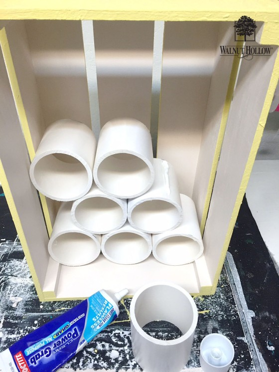 Glue the pvc pipe into the rustic crate using a construction adhesive like power grab glue