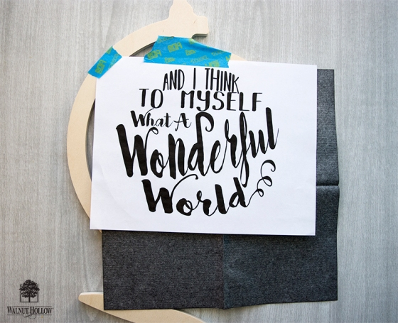 tape the design to the globe with graphite transfer paper